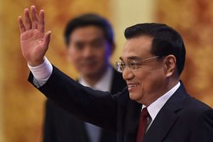 Chinese Premier Li Keqiang waves as he arrives for a press conference after the closing session of the National People's Congress.