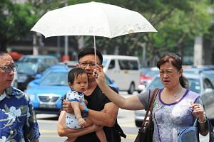 A woman holding up an umbrella for a child under the hot sun on March 17, 2015.