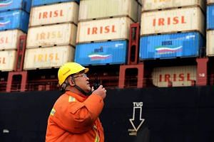A worker watching over cranes as he talks on his interphone at a port in Qingdao, east China's Shandong province, on March 8, 2016.