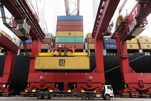 A crane moves a container at a container port in Qingdao, China.