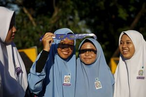 Students watching a partial solar eclipse at the Planetarium in Kuala Lumpur on March 9.
