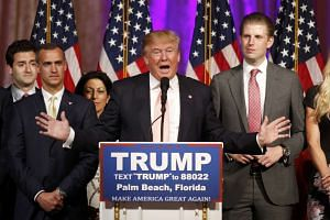 Republican presidential candidate Donald Trump stands between his campaign manager Corey Lewandowski (left) and his son Eric (right) during a news conference in Florida, on March 15, 2016.