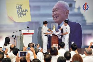 PAP chairman Khaw Boon Wan (far left) and PAP headquarters executive director Alex Yam unveiling the artillery shell casing from a 21-gun salute for Mr Lee's state funeral, which Prime Minister Lee Hsien Loong gave to the party.