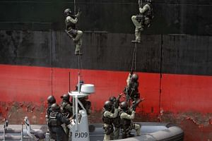 Members of the Singapore Police Force Special Tactics and Rescue Unit (STAR) storm a vessel during a showcase of their counter-terrorism and maritime security measures, at PCG Brani Base on March 18, 2016.