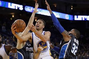 Stephen Curry (centre) goes up for a shot against Evan Fournier (left) and C.J. Watson, on March 7, 2016.