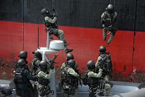 Members of the Singapore Police Force Special Tactics and Rescue Unit, supported by the Police Coast Guard Special Task Squadron, storming a vessel during a showcase of their counter-terrorism and maritime security measures, at the Police Coast Guard