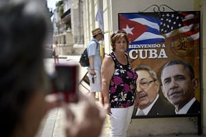 A Cuban woman posing for a picture with a sign showing the images of Cuban and US Presidents Raul Castro and Barack Obama in Havana.
