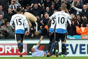 A fan (centre) runs onto the pitch and celebrates with Newcastle United's Serbian striker Aleksandar Mitrovic (2nd left) during the English Premier League football match between Newcastle United and Sunderland at St James' Park in Newcastle-upon-Tyne