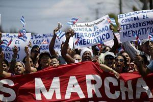 Government supporters shout against a regular march by the 'Ladies in White' dissident group (not pictured), hours before US President Barack Obama arrives for a historic visit, in Havana, March 20, 2016. The signs read
