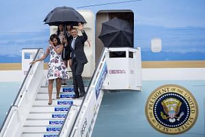 US President Barack Obama disembarking from Air Force One at the Jose Marti International Airport in Havana, Cuba, on March 20, 2016. He is accompanied by First Lady Michelle Obama and his daughters Malia (back left) and Sasha (back right).