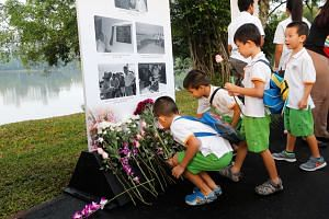 Children lay flowers at a remembrance site for Mr Lee Kuan Yew at Jurong Lake Gardens.