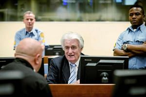 Radovan Karadzic (centre) sits in the courtroom for the reading of his verdict in The Hague, on March 24, 2016.