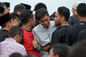 Mr Hatin (centre) grieving at the burial of his two SMRT colleagues at the Muslim cemetery in Lim Chu Kang yesterday.