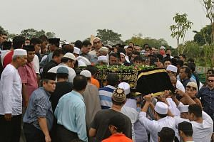 Relatives and friends gather to bid a final farewell to Mr Asyraf. The body of Mr Nasrulhudin being brought to the burial plot at a Muslim cemetery in Lim Chu Kang yesterday.