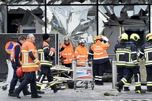 Broken terminal windows are seen at Brussels' airport during a ceremony on March 23, 2016, following the bomb attacks.