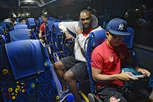 Justin Howard and Wong Wei Long making themselves comfortable yesterday before the team bus left for Woodlands Checkpoint en route to Kuala Lumpur for Game Five of the ABL Finals.