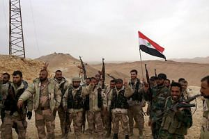 Syrian government soldiers holding the national flag and posing during an operation in Palmyra, Syria on March 26, 2016.