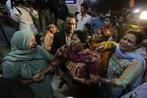 Relatives of the victims of a suicide bomb blast are seen crying outside a hospital in Lahore, Pakistan.
