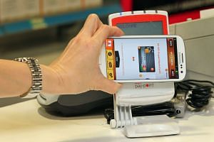 A mobile phone equipped with a Near Field Communications (NFC) capability being used to make purchases.