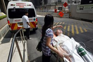 Madam Zeng shielding Mr Aw, who is suing Sembawang Town Council, from sunlight after Monday's hearing.