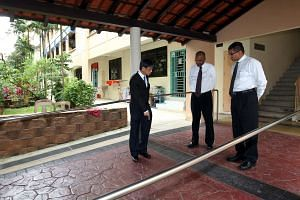 Justice Choo Han Teck (left), who heard the case, inspecting the walkway where Mr Aw Kian Chow fell in 2008. Looking on are Mr Aw's lawyer, Mr N.Srinivasan (centre), and the town council's lawyer, Mr P.E. Ashokan (right). The hearing ended after