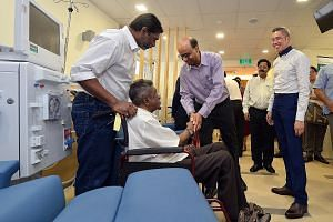 Deputy Prime Minister Tharman Shanmugaratnam greeting patient Sheik Adbul Kadir yesterday at the new dialysis centre in Jurong West. With Mr Tharman is Dr Mooppil Nandakumar (second from right), NKF's director of medical services, and NKF chief execu