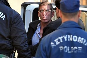 Seif al-Din Mohamed Mostafa is brought by policeman to the court in Larnaca on March 30, 2016.