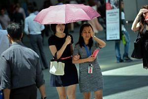 Office workers grimace under the midday sun during lunch hour in the Central Business District at Raffles Place.