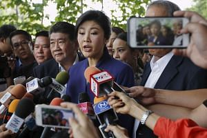 Yingluck Shinawatra arrives at the Supreme Court for a trial on criminal negligence looking into her role in a debt-ridden rice subsidy scheme during her administration.