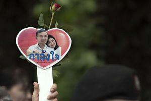 A supporter holds a small heart-shaped placard with a picture of former Thai premier Yingluck Shinawatra and her brother, former prime minister Thaksin Shinawatra.