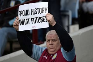 An Aston Villa fan holds a sign questioning his team's performance.