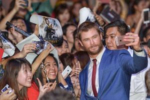 Hollywood star Chris Hemsworth taking a selfie with fans on the red carpet for the premiere of fantasy-action movie The Huntsman: Winter's War.