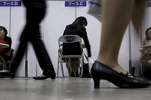 "A job seeker at a job fair held for fresh graduates in Tokyo. Unscrupulous employers reportedly operate a ""bait-and-switch"" policy. They advertise a full-time position with reasonable hours, but later offer the successful applicant a non-regular cont"