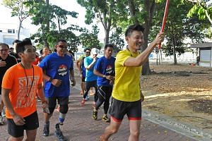 "Mr Baey (in yellow) , the Parliamentary Secretary for the Ministry of Culture, Community and Youth, running with a group that includes ""Blade Runner"" Mr Shariff, Miles for Good project leader Mr Leong (in orange) and other participants in Tampines Ec"