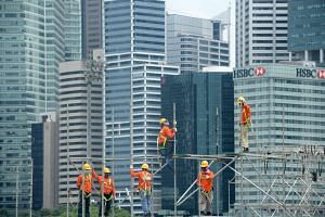 Construction workers building a scaffold against the backdrop of the Central Business District.