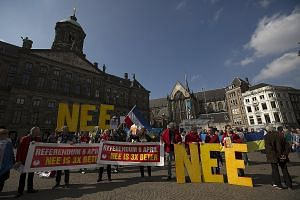 """Demonstrators calling for people to vote """"no"""" in the Dutch referendum on an EU free trade deal with Ukraine during a protest in Dam Square, Amsterdam, on Sunday. The banners read: """"Referendum April 6. No is 3 times better"""", while the big letters toge"""