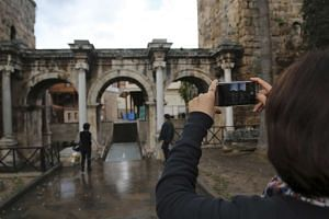 A tourist takes a picture of the Hadrian's Gate, a triumphal arch in the resort city of Antalya, on January 13, 2016.