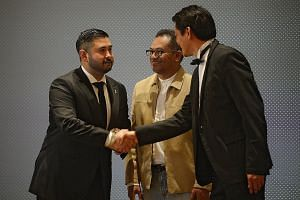 Johor Crown Prince Tunku Ismail Sultan Ibrahim (left) is congratulated by FAS general secretary Winston Lee (right) and FAS president Zainudin Nordin as he receives The Leaders' Leader award during the Pentagon Awards at the Fullerton Bay Hotel last