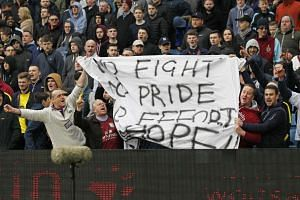 Aston Villa fans hold up a banner in protest .