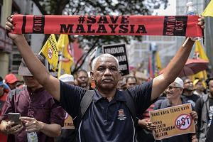 A demonstrator with a Save Malaysia banner during a rally in Kuala Lumpur on April 2. The rally called for the end of the Goods and Services Tax, implemented a year ago, as well as the release of jailed opposition leader Anwar Ibrahim and the resigna