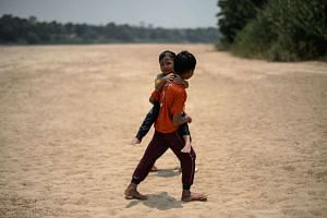 Children walk along the dry banks of the Pahang river in Termerloh, outside Kuala Lumpur, on April 11, 2016, as schools remain closed due to an ongoing heatwave.