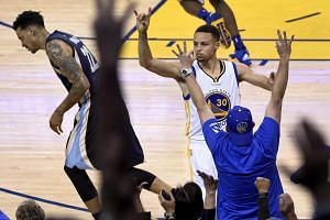 Golden State Warriors player Stephen Curry (right) reacts after making a three-point shot.