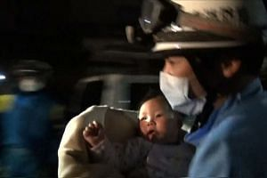 A rescue worker carrying an eight-month-old baby girl after she was pulled from the rubble following an earthquake in Mashiki, Kumamoto Prefecture.