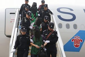 Police escort a group of people wanted for suspected fraud in China as they get off a plane after arriving at Beijing Capital International Airport in Beijing on April 13, 2016.