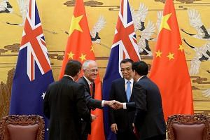 Australian Prime Minister Malcolm Turnbull and Chinese Premier Li Keqiang (both facing camera) at a signing ceremony at the Great Hall of the People in Beijing yesterday. Mr Turnbull is making his first visit to China since he became Prime Minister l