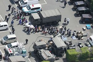 An aerial view shows residents forming a queue to receive meals from defense forces soldiers at the Mashiki town hall in Kumamoto, Japan, on April 15, 2016.