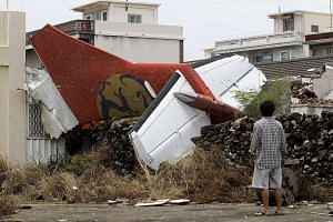 A man stands in his backyard and looks at the wreckage of a TransAsia Airways turboprop plane that crashed on Taiwan's offshore island Penghu, in July 2014.