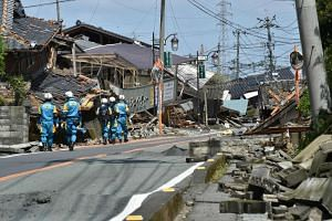 Policemen search for missing persons amongst homes destroyed in the recent earthquakes in Mashiki in Kumamoto prefecture on April 17, 2016.