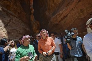 PM Lee, wearing a red-and-white keffiyeh, a symbolic headdress for Jordanians, at historic Petra, with guide Mohammad Qamhiya (in green). From left: Dr Intan, Mr Masagos and Islamic Religious Council of Singapore senior director Albakri Ahmad, speaki