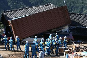 Rescue workers save people from a collaspsed house in Mimami-Aso, Kuammoto prefecture, on April 16, 2016.